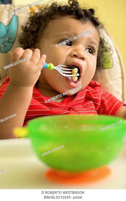Mixed race toddler boy eating in high chair