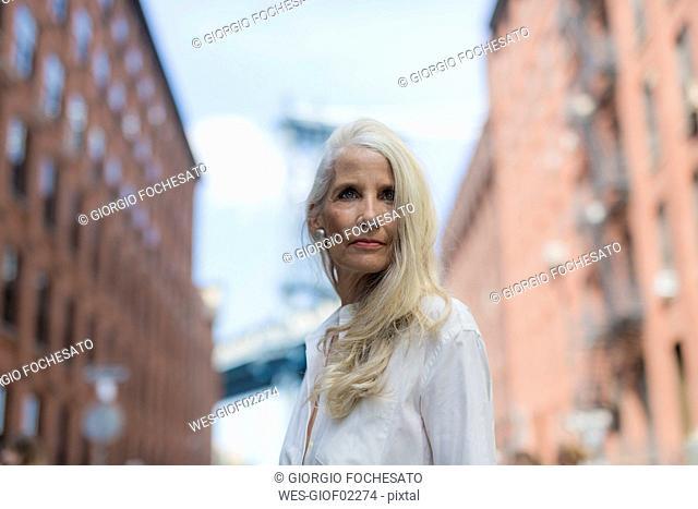 USA, Brooklyn, Dumbo, portrait of mature woman wearing white shirt blouse
