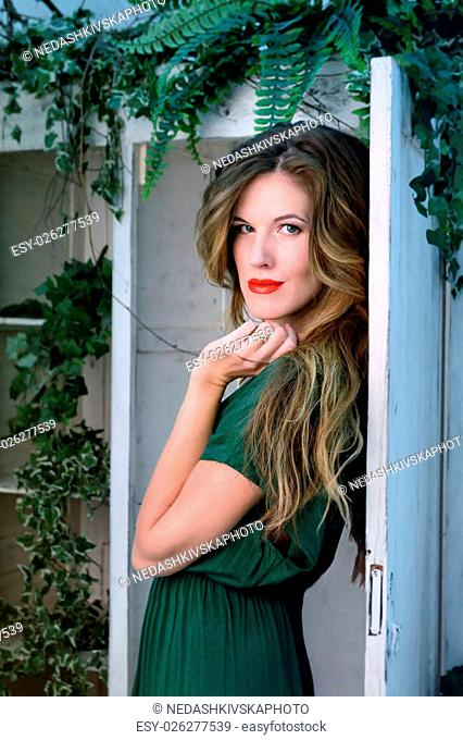 Woman in beauty fashion green gown, long evening dress with plants and flowers