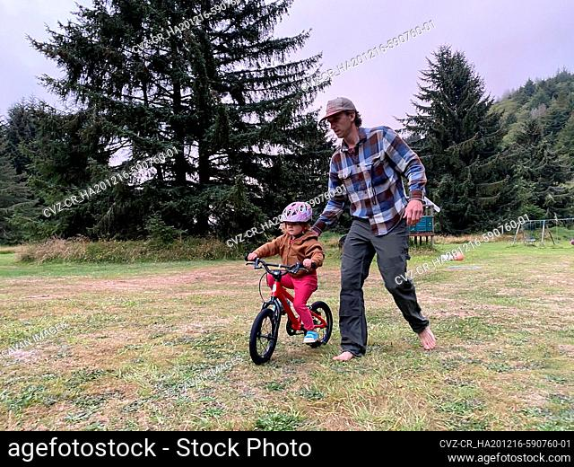A father teaches his daughter how to ride a bike on a grass field