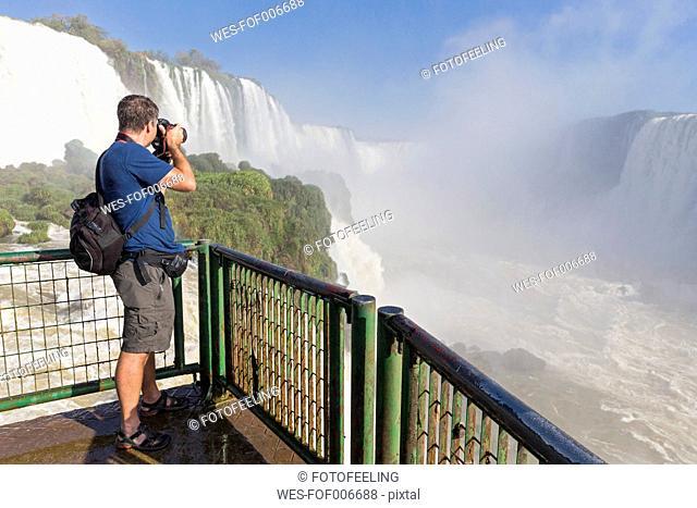 Brazil, Parana, Iguazu National Park, man photographing waterfalls from view terrace