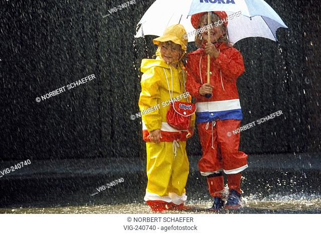 portrait, 2 sisters, 4 and 6 years old, wearing rain-suits and gummiboots, are standing in the rain waiting under a white umbrella in a puddle at the roadside...