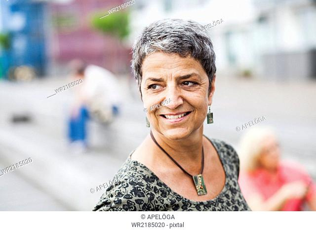 Happy mature woman looking away outdoors