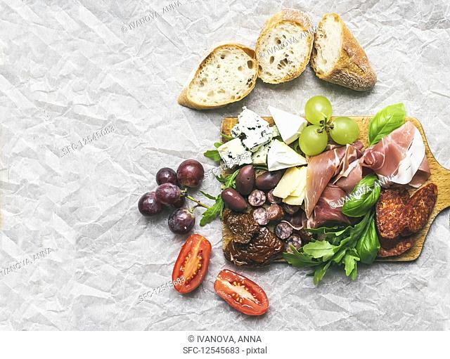 Smoked meat, sausages, cheese, grapes, cherry-tomatoes, olives, basil leaves, arugula, dried tomatoes and baguette slices