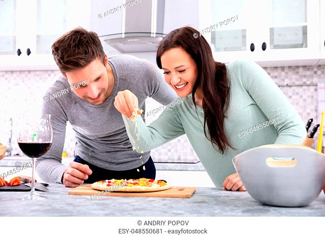 Smiling Couple Sprinkling Cheese On Pizza Standing In Kitchen
