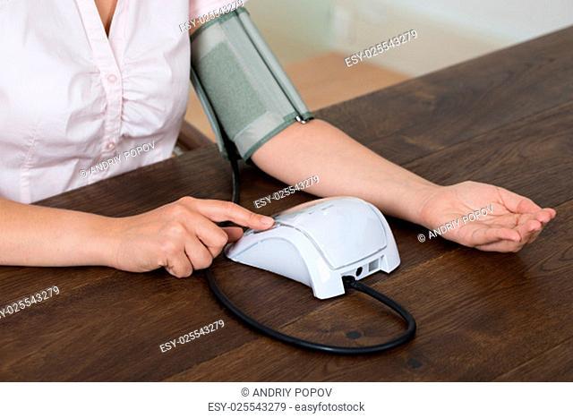 Close-up Of Businesswoman Measuring Blood Pressure At Desk