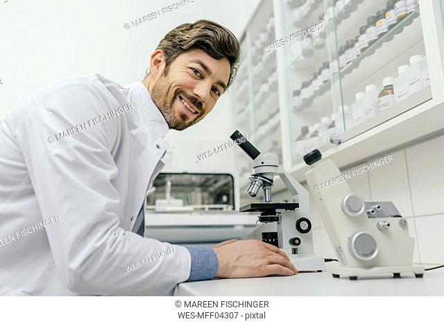 Portrait of smiling man using microscope in laboratory