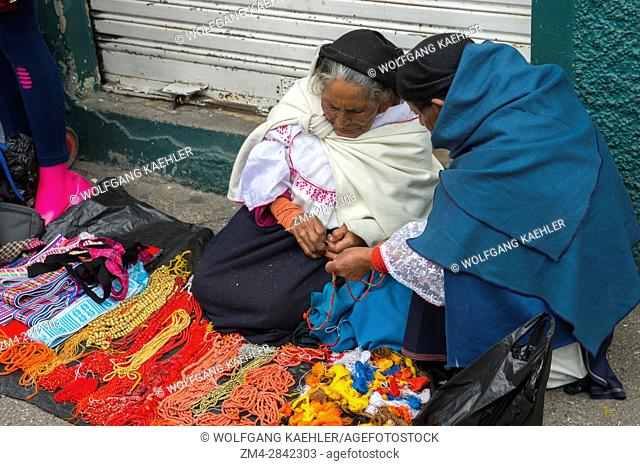 A local woman is selling necklaces on the local market in the town of Otavalo in the highlands of Ecuador near Quito