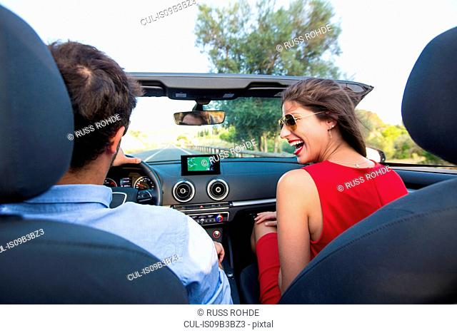 Young couple laughing whilst driving on rural road in convertible, Majorca, Spain