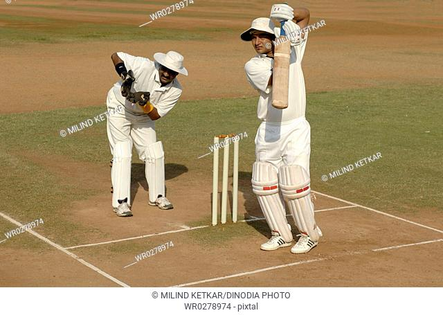 Indian right handed batsman in action playing defensive shot in cricket match MR705L
