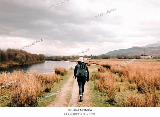 Trekker walking by Loch Lomond, Trossachs National Park, Canada