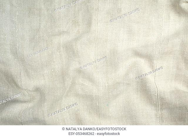 fragment of a very old linen homespun fabric with waves on the surface, full frame
