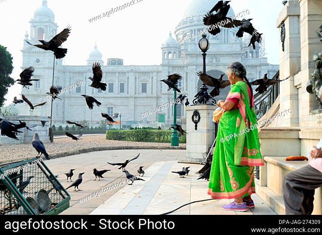 Woman feeding crows, Victoria Memorial, Kolkata, West Bengal, India, Asia
