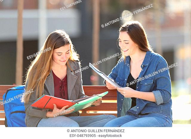 Two happy students studying reading notes sitting on a bench in a park