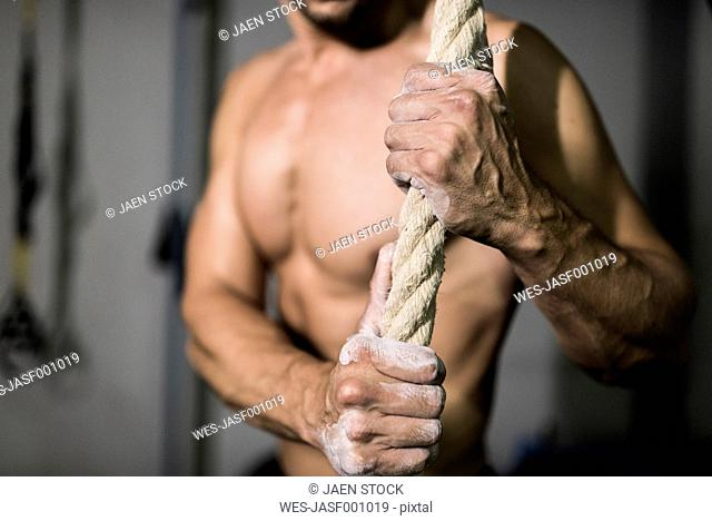 Athlete with chalk in hands holding rope