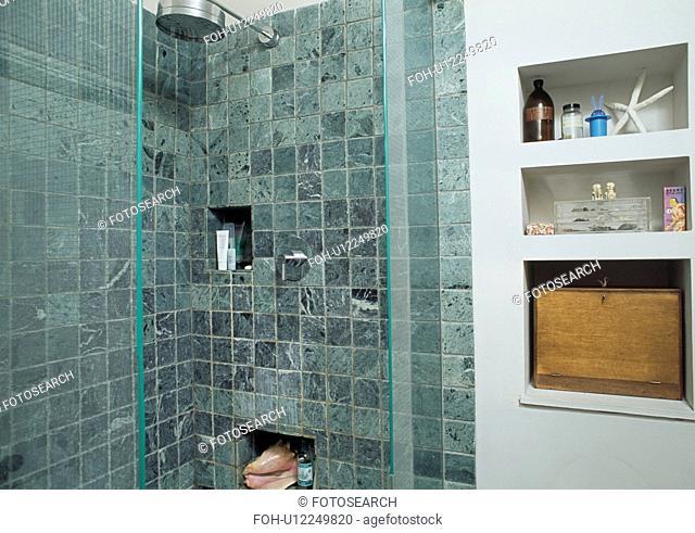 Open shelves beside shower with limestone tiles