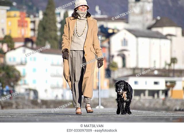 Elegant woman walking on the street with her dog and with a village in background