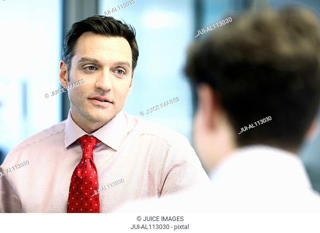 Businessman talking to teenage boy