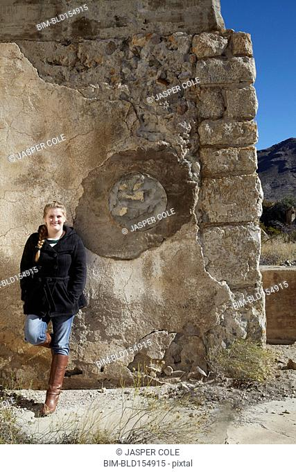 Tourist smiling near relief sculpture on wall of ruins