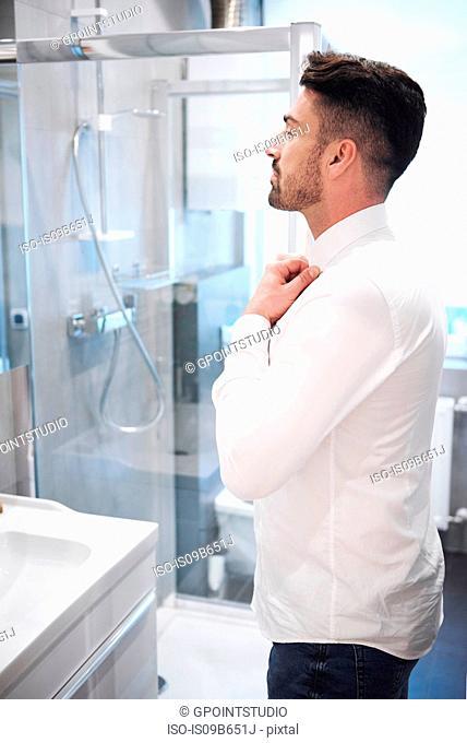 Man putting on shirt, fastening buttons