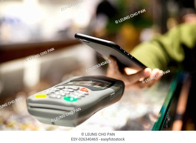 Woman using mobile phone for pay the bill