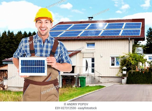 Young Repairman Holding Solar Panel Outside The House With Solar Panels On Roof