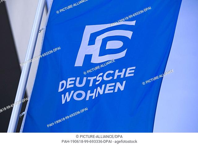 18 June 2019, Hessen, Frankfurt/Main: The logo of the real estate group Deutsche Wohnen can be seen in the morning on a flag in front of the entrance to the...