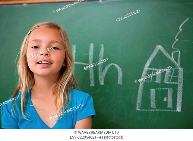 Blonde schoolgirl posing in front of a blackboard