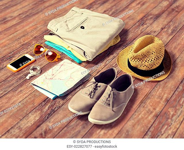 summer vacation, tourism and objects concept - close up of clothes, smartphone, personal stuff and travel map on wooden floor