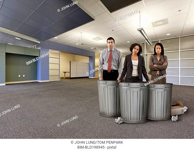 Business people standing with garbage cans in empty office
