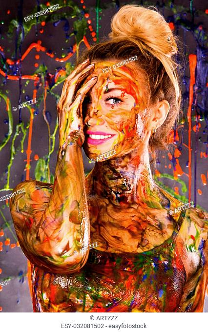 Beautiful young woman covered with multicolored paints
