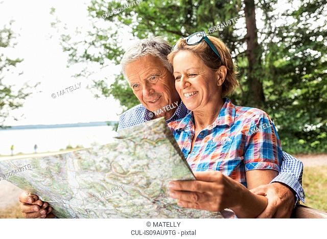 Couple in forest, looking at map, smiling
