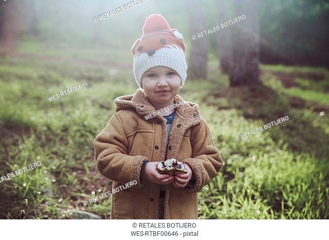 Portrait of boy eating Berliner in forest