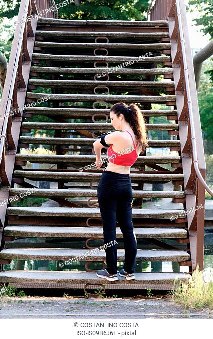 Young female runner standing on stairway looking at smartphone armband