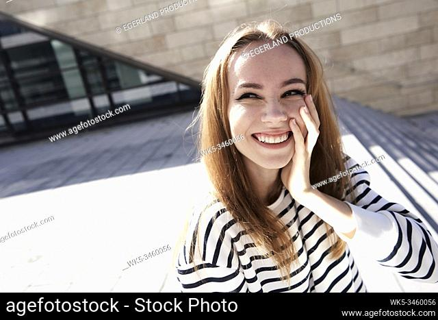 Portrait of young woman with hand on cheek. Munich, Germany