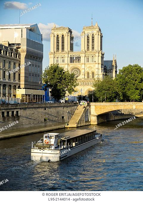 Seine river and tourists boat passing by the Cathedral of Notre Dame in Paris, France