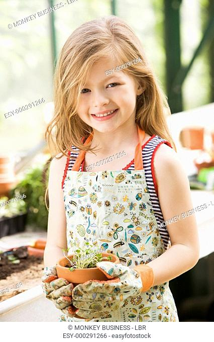 Young girl in greenhouse holding potted plant smiling