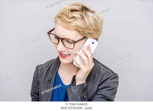 Portrait of smiling blond woman telephoning with smartphone in front of grey background