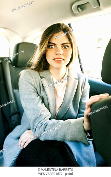 Portrait of young businesswoman sitting on backseat of a car