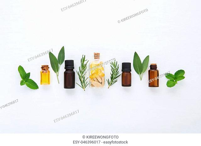 Bottle of essential oil and herbal medicine with fresh herbs sage, rosemary, mint and spearmint setup with flat lay on white wooden table. top view