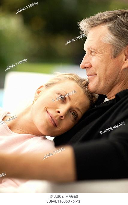 Mature couple relaxing on outdoor sofa, close up
