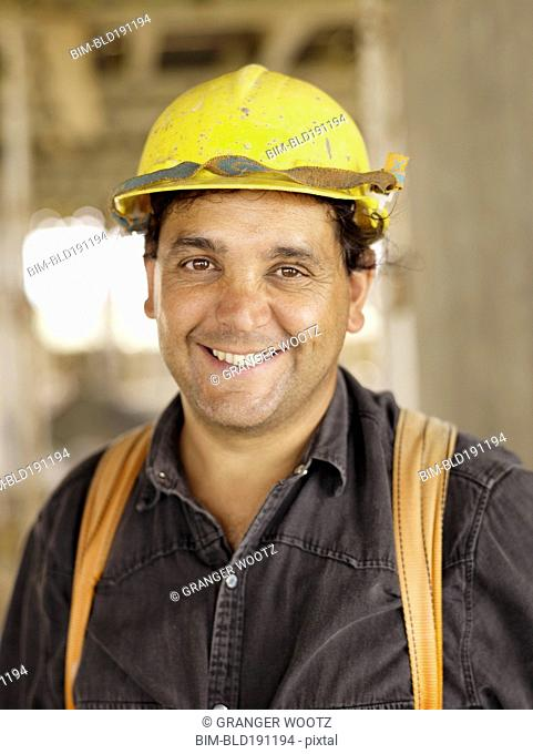 Hispanic worker smiling on construction site