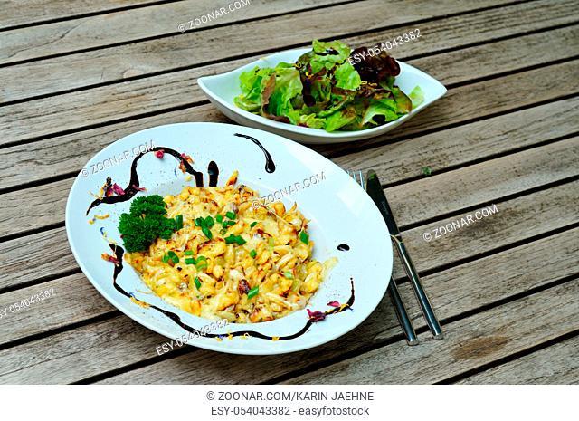 Kaesespaetzle mit Salat auf einem Tisch. Cheese spaetzle on a plate with a salad