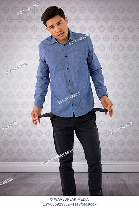 Businessman holding empty broke pockets in room
