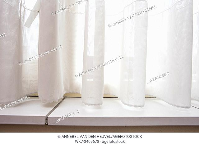 Lace curtain and windowsill close-up with sunlight and clean