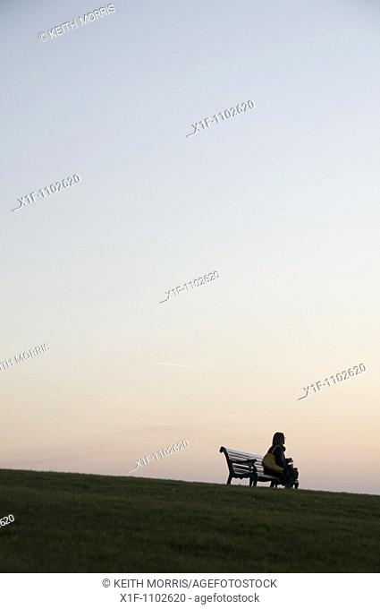 Woman sitting alone by herself on a park bench at twilight, Aberystwyth Wales UK