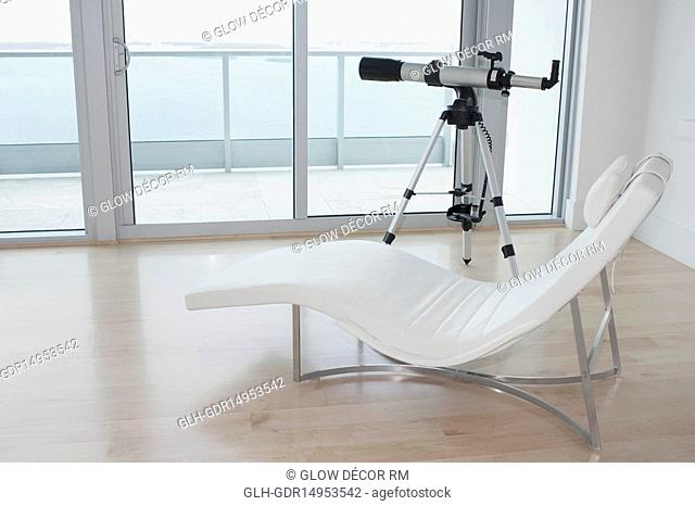 Telescope with a lounge chair in a room