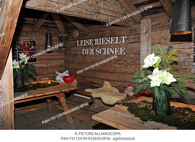"""28 November 2019, Austria, Going: Christmas decoration and a wall decoration with the inscription """"""""Leise rieselt der Schnee"""""""" (The snow trickles quietly) at..."""