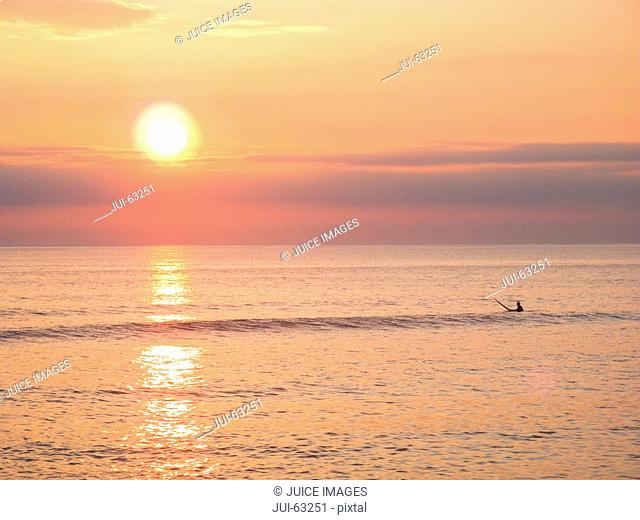 Surfer on surfboard at Sunset