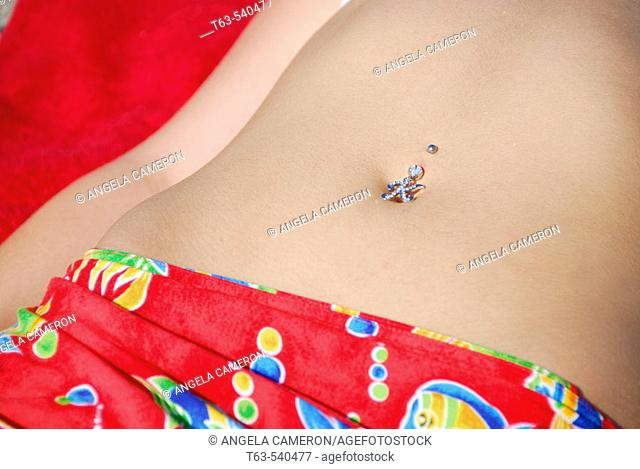 girl laying on beach with belly piercing of 'k'